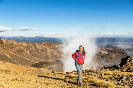 New Zealand Tongariro Alpine Crossing Hiking trek hiker woman with bag and outdoor jacket tramping in volcanic steam vents fumaroles background. Summer travel vacation adventure trekking girl hike. Stock Photo