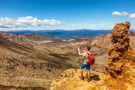 New Zealand Tongariro Alpine Crossing hike trail nature landscape hiker man taking picture of background. Happy tramper filming phone photo at volcanic mountains . Summer adventure Travel.