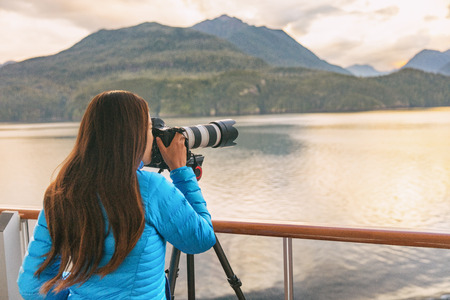 Travel photographer with professional telephoto lens camera on tripod shooting wildlife in Alaska, USA. Scenic cruising inside passage cruise tourist vacation adventure. Woman taking photo picture.