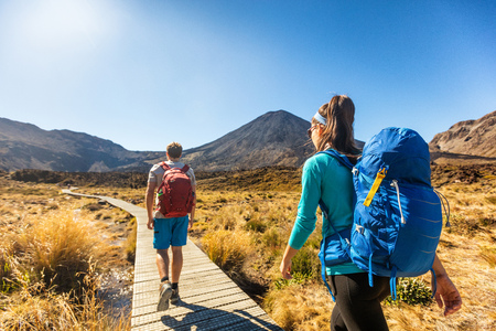 New Zealand Hiking Couple Backpackers Tramping At Tongariro National Park. Male and female hikers hiking by Mount Ngauruhoe. People living healthy active lifestyle outdoors Stock Photo