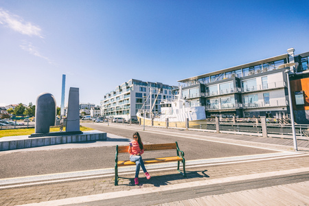 Reykjavik city lifestyle people watching street scene, Iceland. Woman using smart phone relaxing on bench at reykjavík harbour near modern condo building downtown. Summer Europe lifestyle.