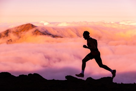 Trail runner athlete man running in nature landscape. Silhouette of male person training on mountains in cold weather with pink clouds at sunset. Amazing mountain peaks in the background. Stockfoto