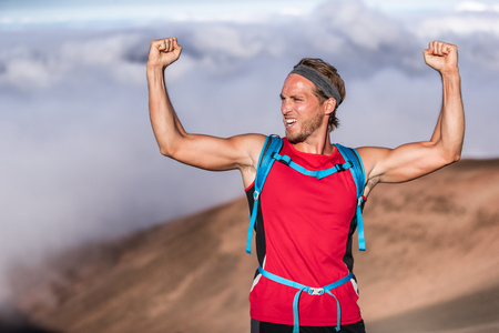 Fitness achievement fit athlete man screaming with fists up in the air winner arms up. Success in sport hiker on summit of mountain - goal challenge. Stockfoto