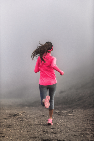 Run fit woman runner running on trail path in mountains in fog and clouds - morning jogging training in pink sportswear clothes.