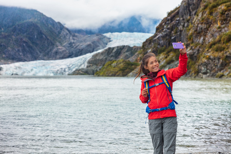 Tourist woman taking selfie photo at Mendenhall glacier in Juneau, Alaska. Famous tourism destination on Alaska cruise, USA travel.