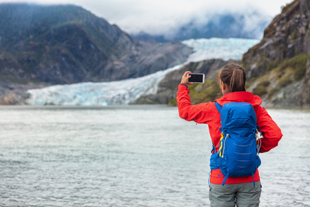 Alaska travel cruise ship tourist taking photo with phone. Hiker with backpack at Mendenhall glacier in Juneau visiting famous attraction destination. Glacier arm melting in lake.