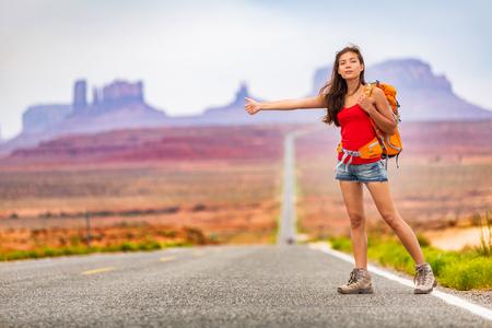 Donna di viaggio zaino in spalla autostop in viaggio su strada autostop un passaggio dall'auto in una natura incredibile del paesaggio. Arizona, Utah, Stati Uniti d'America. Avventura per le vacanze estive.