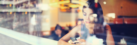 Mobile phone woman using smartphone texting in city cafe urban businesspeople lifestyle banner panorama. Asian usinesswoman sitting by window with reflections background.