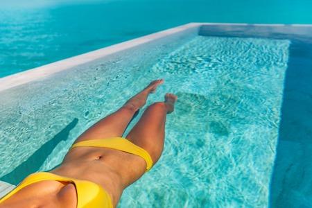Sexy bikini lichaam vrouw ontspannen zwemmen in luxe infinity pool van Tahiti resorthotel liggend in water drijvend in gele bikini. Gebruind slank lichaam.