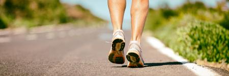 Fit run runner man jogging feet closeup running shoes banner panorama. Athletes legs walking on street for summer marathon. Archivio Fotografico