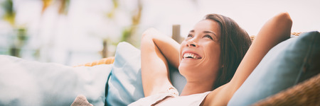 Relaxing home lifestyle happy woman in relax luxury hotel room sofa lying back with arms behind head smiling. Asian girl in comfortable lounging chair travel living.