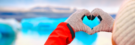 Winter fun landscape banner panorama. Love for Iceland - hand heart shape over Jokulsarlon lake glaciers icebergs. Woman showing sign gesture with iceberg on glacial lagoon / glacier. Banque d'images - 122979273