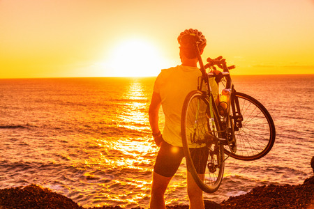 Triathlon road bike cyclist carrying bicycle watching sunset after outdoor race training by ocean coast landscape. Man athlete biking outdoors.