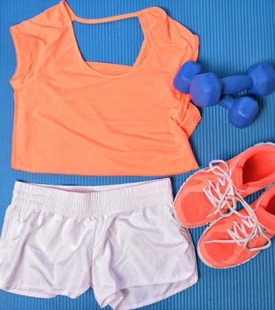 Gym clothes for fitness strength training workout layed out on blue exercise mat top view. Orange matching t-shirt and shoes, white shorts, dumbbells weights. Stock fotó
