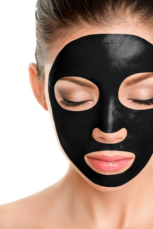 Charcoal face mask peel off facial treatment Asian beauty woman using chemical black mask therapy.