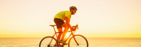 Triahtlon athlete man biking on road racing bike ride outdoors at sunset banner panorama landscape. Cyclist exercising outside with sunglasses and helmet.