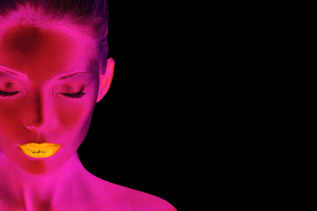 Pink neon body paint blacklight glow in the dark futuristic Asian beauty woman model in nightclub wearing gold lips makeup. Black background.