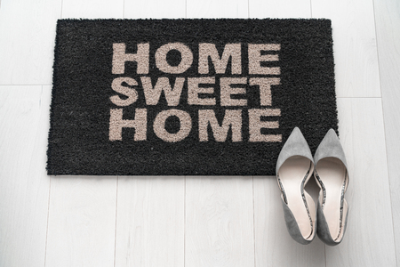 Modern condo businesswoman high heel shoes at home on entrance doormat saying Home Sweet Home welcoming homeowner after a day at work at new house background concept. Fashion grey suede kitten heels. Stockfoto