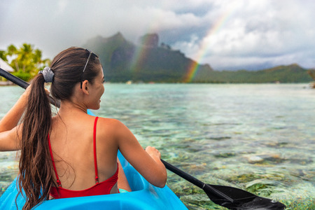 Kayak woman watersport activity tourist enjoying kayaking in Bora Bora at Mount Otemanu, Tahiti, French Polynesia. Active ocean sport lifestyle. Stock Photo