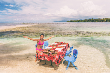 Beach picnic motu tour in Bora Bora, Tahiti, French Polynesia. Happy tourist woman eating at table in ocean water feet in sand for summer lunch. Travel lifestyle.