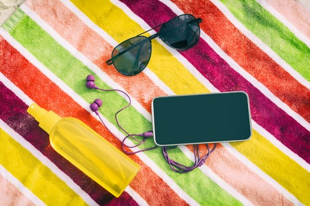 Beach vacation summer essentials top view of objects on colorful towel background. What to bring on travel holidays: Music mobile phone, earphones, sunglasses, sunscreen.