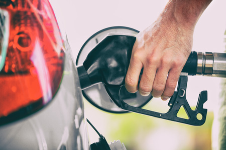 Gas pump person pumping fuel filling car tank at gas station. Man hand holding nozzle refuel. Price of gasoline. Foto de archivo - 123633372