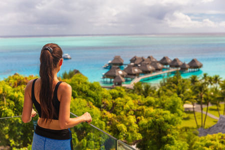 Luxury Bora Bora hotel resort woman tourist overlooking view of overwater bungalows villas on Tahiti ocean, French Polynesia. Stock Photo