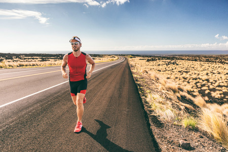 Sport runner man athlete running in triathlon tri suit training for Iron man on Hawaii. Fit male triathlete exercising cardio at sunset on road in nature landscape on Big Island, Hawaii. Standard-Bild
