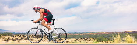 Triathlon biking man cycling on road bike in nature background banner. Cyclist triathlete riding bicycle in ironman competition. Panorama header crop for landscape copy space. Stockfoto