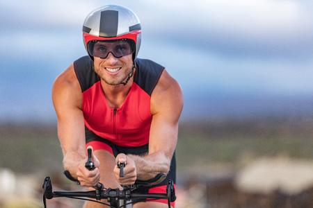 Triathlon biking man cyclist portrait riding bike. Male triathlete cycling on triathlon bike. Fit man professional athlete on triathlon bicycle wearing time trial helmet for ironman race. Stockfoto