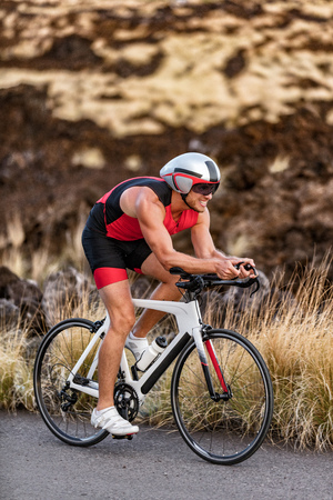 Triathlon professional cyclist man cycling road racing bike in time trial helmet and compression tri suit in Hawaii landscape for Kailua-Kona ironman. Triathlete biking in nature. Stockfoto
