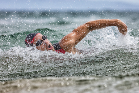 Triathlon swim tired swimmer swimming in ocean in wave and rain storm . Professional male triathlon swimmer wearing cap, goggles and red triathlon tri suit training for ironman breathing out of water.