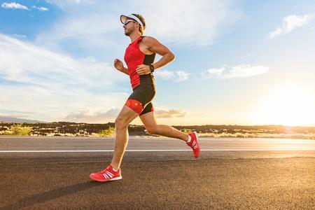Triathlon - Triathlet, der im Triathlon-Anzug für das Ironman-Rennen läuft. Männlicher Läufer, der auf Big Island Hawaii trainiert. Sonnenuntergang.