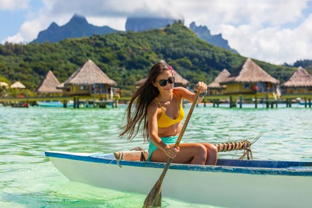 Outrigger Canoe - woman paddling in traditional French Polynesian Outrigger Canoe for recreation sport watersport competition. Bora Bora with Mount Otemanu and overwater bungalow resort hotel. Stock fotó