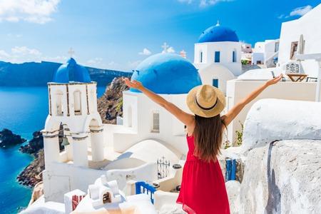 Europa reisen glückliche Urlaubsfrau. Mädchentourist, der Spaß mit offenen Armen in Freiheit im Santorini-Kreuzfahrturlaub hat, europäisches Sommerziel. Person mit rotem Kleid und Hut.
