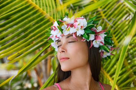 Beauté exotique femme bien-être relaxante les yeux fermés sur la plage tropicale avec accessoire cheveux couronne de fleurs de Tahiti. Bora Bora, Polynésie française.