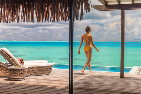 Luxury Bora Bora resort hotel woman walking on her private terrace deck of overwater bungalow villa with infinity pool view on turquoise ocean - honeymoons suite.