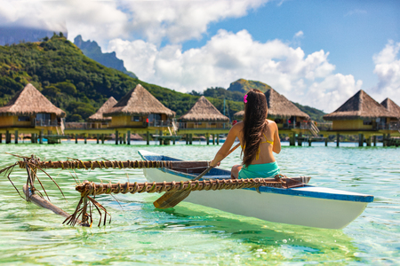 Outrigger Canoe - woman paddling in traditional French Polynesian Outrigger Canoe for recreational activity and watersport competition. Bora Bora with famous Mount Otemanu and overwater bungalow resort hotel sport lifestyle .