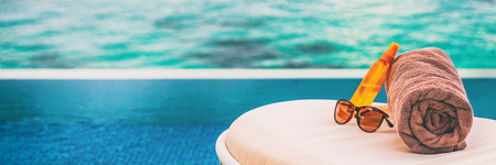 Luxury vacation banner background of sunscreen, sunglasses for sun protection on towel and lounger at hotel infinity swimming pool for sun tan summer relaxation panoramic banner.