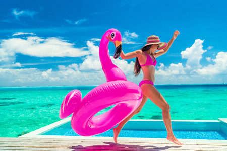 Vacation fun woman in bikini with funny inflatable pink flamingo pool float running of joy jumping by infinity swimming pool. Girl enjoying travel holidays at resort luxury overwater bungalow travel. Banque d'images
