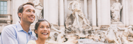 Smiling couple of multiracial people at Trevi fountain in Rome, Italy. Europe summer travel elegant Asian woman with Caucasian man happy portrait banner panorama. Stockfoto