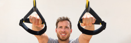 Fitness man trx banner suspension resistance straps training. Athlete holding handles doing inclined pull-ups for back and biceps muscles at gym. Panorama horizontal crop. Banco de Imagens