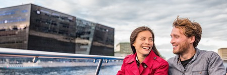 Copenhagen tourists couple on city boat cruise tour of the black diamond Royal library, famous architecture building, Denmark, Europe travel. Panoramic banner of people traveling lifestyle. Reklamní fotografie