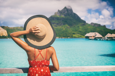Beach vacation travel getaway summer holiday woman looking at view of Mt Otemanu on Bora Bora luxury hotel on romantic honeymoon. Tourist holding hat from behind enjoying Tahiti, French Polynesia. Stock Photo