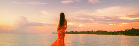 Sunset beach banner woman relaxing at dusk looking over soft pink sky clouds serene wellness zen landscape banner panorama - Tropical holidays in paradise. Reklamní fotografie