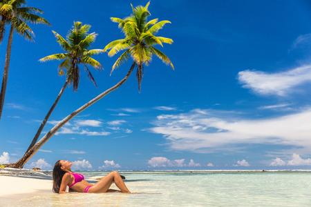 Mujer de bronceado de paraíso de vacaciones en la playa relajante acostado bronceado en el fondo de verano idílico tropical en el Caribe con cielo azul y palmeras.
