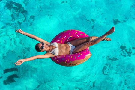 Summer vacation fun woman relaxing in donut swimming pool float with arms open in freedom and happiness enjoying tropical travel holidays in blue ocean background.