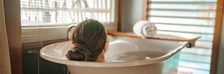 Luxe bad vrouw ontspannen in warme badkuip in hotel resort suite kamer genieten van verwennerij spa moment levensstijl banner panorama. Stockfoto