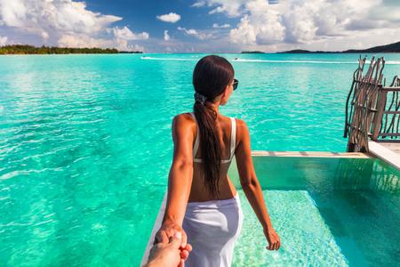 Sígueme en la playa pareja hombre sosteniendo la mano de la novia siguiendo a la mujer a la piscina de vacaciones en el océano azul en Bora Bora, Tahití, Polinesia Francesa.