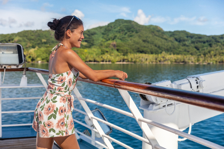 Cruise ship vacation woman relaxing in sun enjoying boat deck resting on railing of looking at Tahiti island landscape. Happy Asian girl on French Polynesia holiday travel. 免版税图像